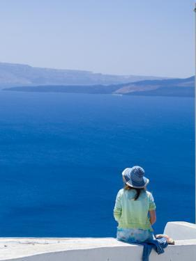 A Tourist Sits on a Stucco Wall Overlooking the Aegean Sea by Richard Nowitz