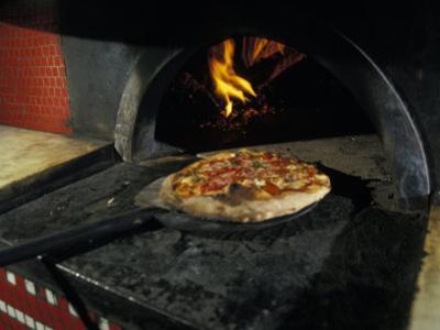 Pizza Comes Out of a Brick Oven in a Restaurant in Rome, Italy