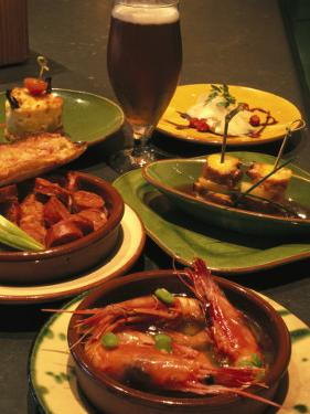 Several Dishes of Tapas and a Beer in a Spanish Restaurant by Richard Nowitz