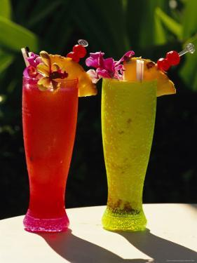 Two Tall Cold Tropical Drinks Garnished with Fruit and Flowers by Richard Nowitz