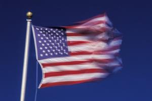American Flag is Blurred with the Motion of the Wind against the Blue Sky by Richard T. Nowitz