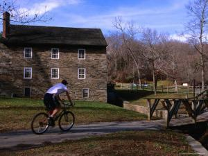 Man Cycling Past Building in Rock Creek Park, Washington Dc, USA by Rick Gerharter