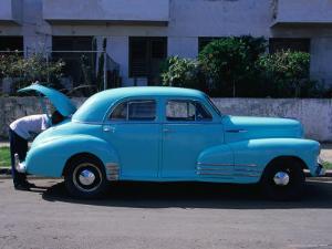 Man Looking in Boot of a Blue 1948 Chevrolet, Vedado, Cuba by Rick Gerharter