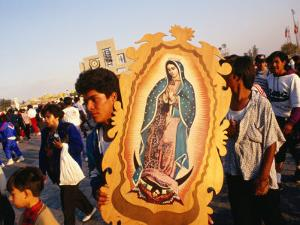 Pilgrim Carrying Icon of Virgin Mary at the Basilica De Guadalupe, Mexico City, Mexico by Rick Gerharter