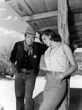 RIO BRAVO, 1959 directed by HOWARD HAWKS On the set, John Wayne and Angie Dickinson (b/w photo)