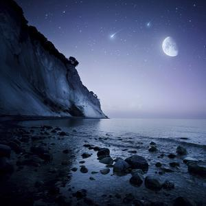 Rising Moon over Ocean and Mountains Against Starry Sky