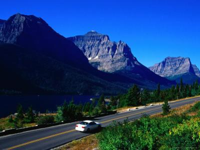 Car Driving on Road with Mountain Range Glacier National Park, Montana, USA by Rob Blakers