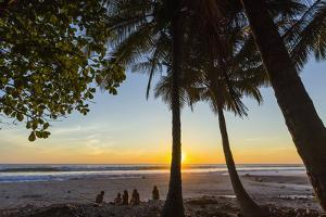 People by Palm Trees at Sunset on Playa Hermosa Beach, Santa Teresa, Costa Rica by Rob Francis