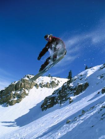 Person Holding Snowboard While Jumping