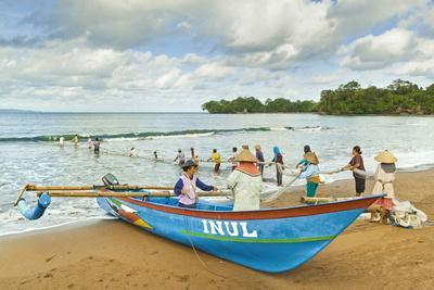 Outrigger Fishing Boat and People Pulling Net in by Hand to Shore Near Batu Karas