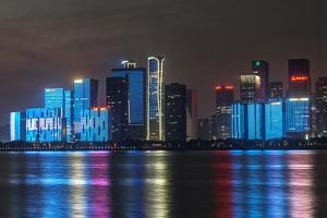 China, Zhejiang, Hangzhou. City skyline at twilight. by Rob Tilley