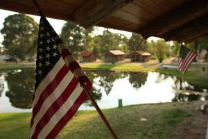 American Flags Hang from Cabins at the Spring Creek Campground and Trout Ranch by Robb Kendrick