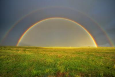 A double rainbow in a meadow. by Robbie George