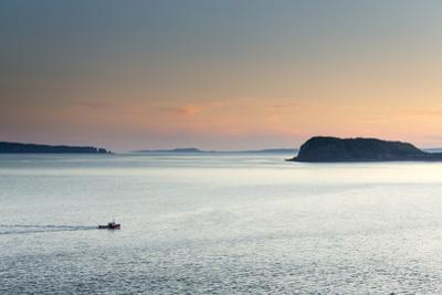 A Fishing Boat Cruises Through Flat Water at Dusk by Robbie George