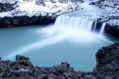 A short yet powerful cascade pours into a cerulean pool. by Robbie George