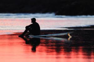 A Surfer Sits on His Surfboard While Watching the Waves at Sunset by Robbie George