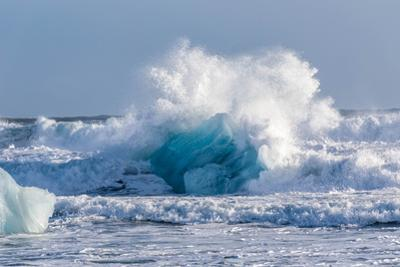 A wave crashes over a deep blue iceberg. by Robbie George