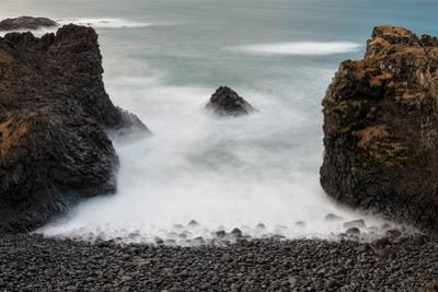 Basaltic rock pillars channel the North Atlantic ocen into a pocket cove. by Robbie George
