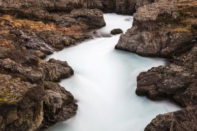 Blurred water flows through Barnafoss. by Robbie George