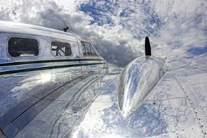 Clouds and Sky Reflecting Off the Shiny Silver Surface of An Airplane by Robbie George