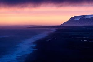 Gentle waves climb the black sand shoreline under cotton candy skies. by Robbie George