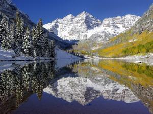 The Maroon Bells Casting Reflections in a Calm Lake in Autumn by Robbie George