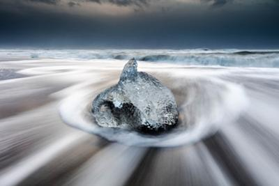 Water retreats back to the sea around a frozen obstacle. by Robbie George