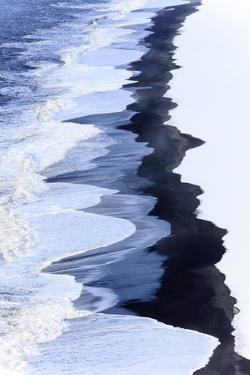 Waves etch away the fresh layer of snow. by Robbie George