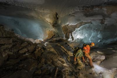 Expedition team members descend from ice to rock inside a limestone cave system by Robbie Shone