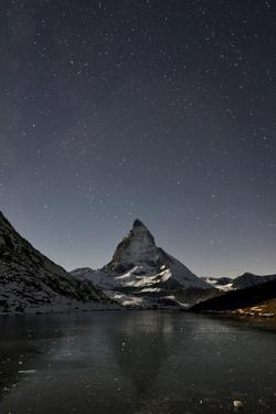 The Matterhorn looms above a frozen lake. by Robbie Shone