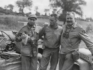Robert Capa (Left) and Ernest Hemingway (Right) with their Driver U.S. Army Driver