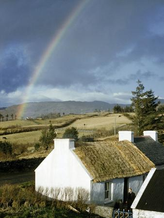 A Rainbow Arches over a Thatched White Cottage and Nearby Fields