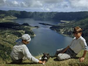 Men with Puppy Overlook Hourglass-Shaped Lakes in Volcanic Crater by Robert Sisson