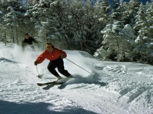 Skiers Heading Downhill Cut Through Powdery Snow by Robert Sisson