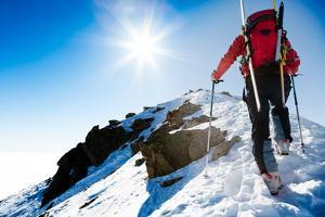 Mountaineer Walking up along a Snowy Ridge with the Skis in the Backpack. in Background a Shiny Bri by Roberto Caucino