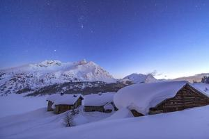 A Starry Night Covering the Spluga Huts Submerged in Snow Near the Maloja Pass by Roberto Moiola