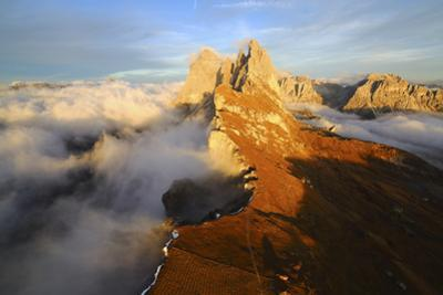 Aerial Shot from Seceda of Odle Surrounded by Clouds at Sunset in the Dolomites by Roberto Moiola
