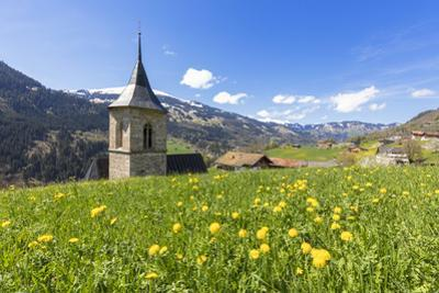 Bell tower surrounded by wildflowers and meadows in spring, Luzein, Switzerland by Roberto Moiola