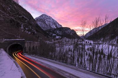 Car trail lights on the icy road at dawn, Campodolcino, Spluga valley, Sondrio province, Valtellina by Roberto Moiola