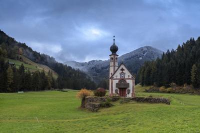 Clouds on Church of Ranui surrounded by meadows and woods in the fall, St. Magdalena, Funes Valley, by Roberto Moiola