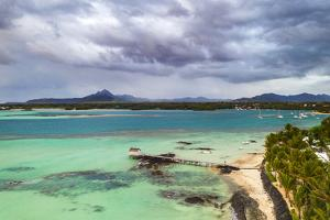 Clouds over lagoon and pier by a palm fringed beach, Trou d'Eau Douce, Mauritius by Roberto Moiola