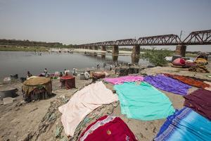 Colorful Clothes Drying in the Sun on the Banks of the River Yamuna by Roberto Moiola