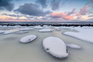 Dawn on the Cold Sea Surrounded by Snowy Rocks Shaped by Wind and Ice at Eggum by Roberto Moiola