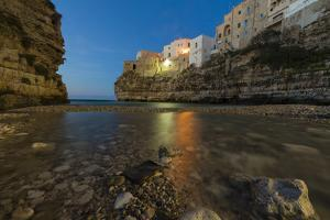 Dusk lights on the clear sea framed by the old town perched on the rocks, Polignano a Mare, Provinc by Roberto Moiola