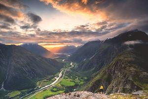 Elevated view of man standing on Romsdalseggen ridge admiring Rauma valley by Roberto Moiola