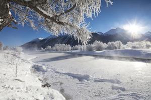 Frost on trees frame the snowy landscape and frozen river, Inn, Celerina, Maloja, Canton of Graubun by Roberto Moiola