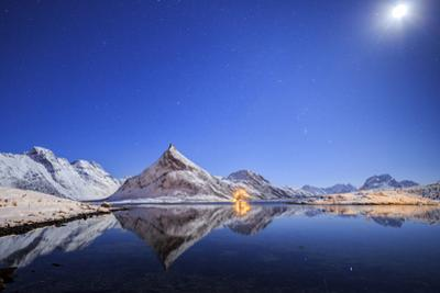Full moon and stars light up snow capped peaks reflected, Volanstinden, Fredvang, North Norway by Roberto Moiola