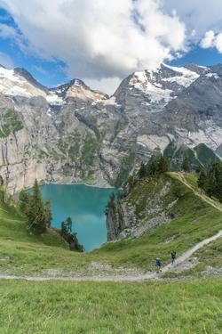 High angle view of two hikers walking on path above Oeschinensee lake, Switzerland by Roberto Moiola