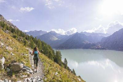 Hiker on path towards Rifugio Bignami beside the dam and water basin of Alpe Gera, Malenco Valley,  by Roberto Moiola