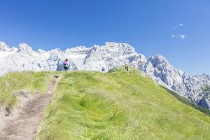 Hikers proceed on the path to the rocky peaks, Doss Del Sabion, Pinzolo, Brenta Dolomites, Trentino by Roberto Moiola